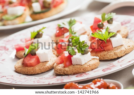 Mediterranean style canape with feta cheese and tomato - stock photo