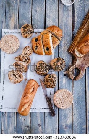 Mediterranean whole wheat bread concept. Include variety bread focaccia with olives, baguette sandwich, sunflowers seeds buns, chapatti sliced, hamburger bread  from above on blue wooden table. - stock photo