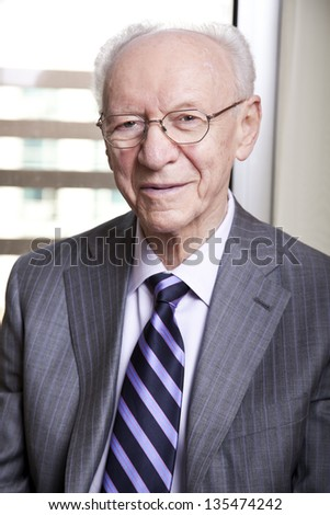 Medium close-up portrait of a senior businessman (in his 80's) smiling to the camera wearing a suit and tie, as well as old fashion glasses. - stock photo