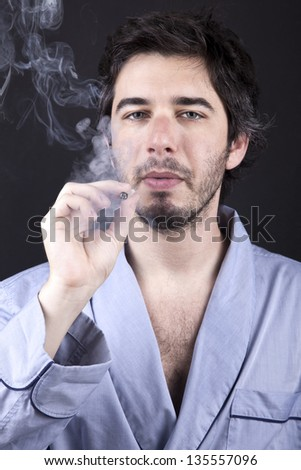 Medium closeup of an adult man (30 years old), numbingly gazing at the camera, concentrated in smoking a marijuana spliff (aka reefer; joint). Dark gray background. - stock photo