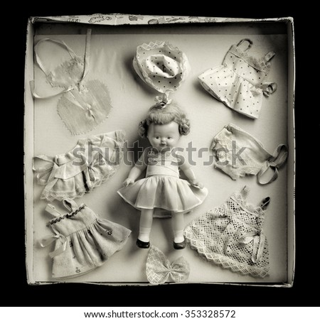 Medium format film photography shot with. Warm tone. Front view of vintage box doll game against black background. - stock photo