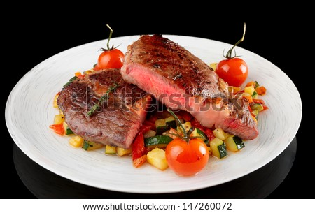Medium fried steak with fried vegetables shot on black background - stock photo