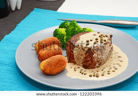 Medium grilled beef steak with pepper sauce and potato croquettes, served on a plate - stock photo