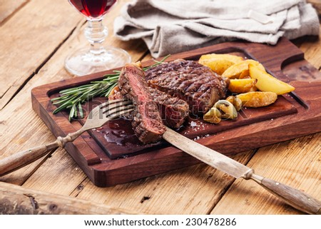 Medium rare grilled Beef steak Ribeye with roasted potato wedges on cutting board on dark wooden background - stock photo