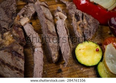 Medium rare grilled rib eye steak on wooden rustic cutting board - stock photo