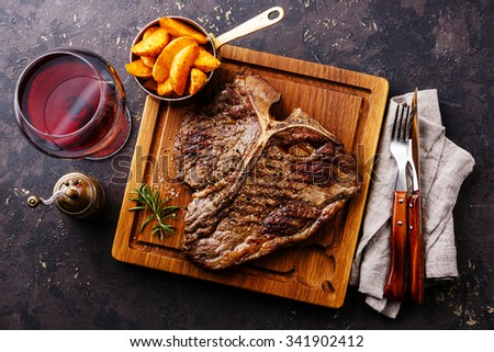 Medium rare Grilled T-Bone Steak with potato wedges and wine on serving board block on dark background - stock photo