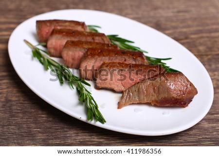 medium roast rib-eye steak with pepper, thyme and salt - stock photo