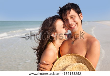 Medium shot of Latin young Man and Woman laughing on Florida Beach - stock photo