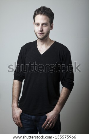 Medium shot studio portrait of a caucasian adult man in his early 30's over gray background. He seems to be in a good mood, looking at the camera with the hint of a smile.