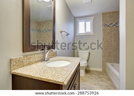 Medium sized bathroom with tile floor, full bath shower, and a window.
