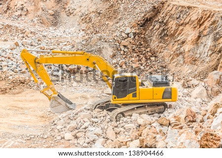 Medium sized excavator with rock background - stock photo