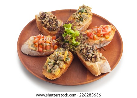 Medley bruschetta topping with sauteed mushroom/ garlic butter clam/ tomato salsa on wood plate, isolated on white. - stock photo