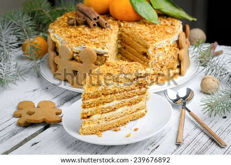 Medovik or honey cake decorated with gingerbread man cookies, tangerines and spices on white round plate. Christmas food still life - stock photo
