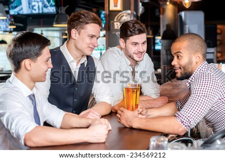 Meet at the bar. Three cheerful friends met at the bar until the bartender takes a glass of beer on the bar counter - stock photo