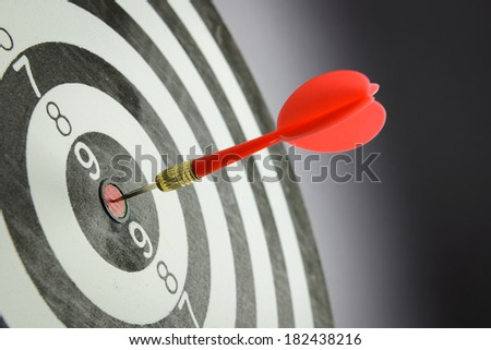 Meet target concept using dart pinned at the bullseye of dartboard - stock photo