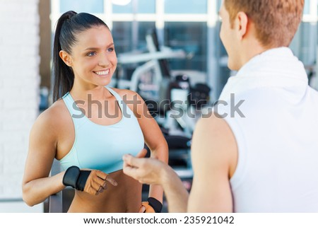 Meeting good friends in gym. Beautiful young sporty couple talking and smiling while standing in gym  - stock photo