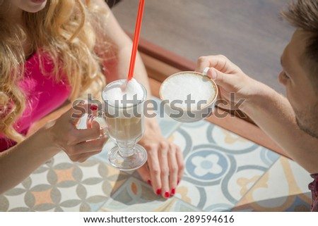Meeting of couple with a cup of latte and capiccino in coffee bar. Man and woman resting on weekends. - stock photo