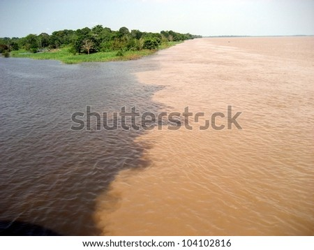 Meeting of the Rio Amaturá (black water) and the Rio Solimoes (muddy water) at Amaturá in the Amazon, Brazil - stock photo