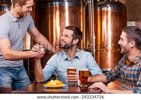 Meeting old friend. Three happy young men sitting in beer pub together while two of them handshaking - stock photo