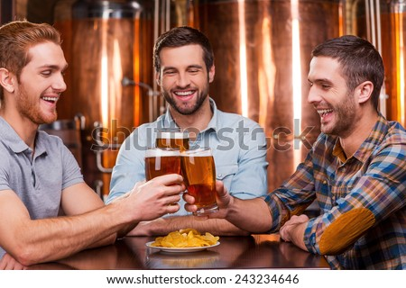 Meeting old friends in bar. Three happy young men in casual wear toasting with beer and smiling while sitting in beer pub together - stock photo