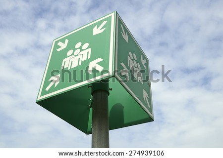 Meeting or assembly point sign on blue sky - stock photo