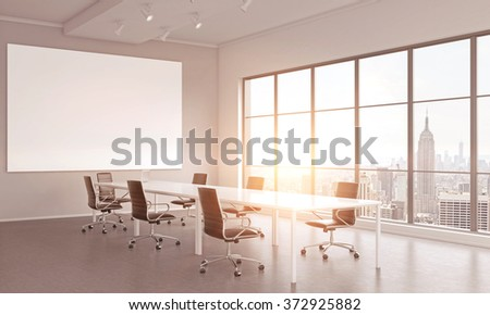 meeting room with a table in the center, a laptop on it, seven black chairs around it. A blank frame on the white wall. Window to the right. Filter. Concept of negotiations. 3D rendering - stock photo