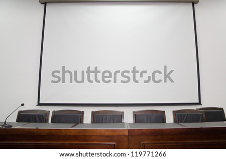 meeting room with blank projection screen - stock photo