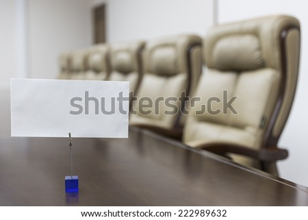 Meeting room with empty card on table - stock photo