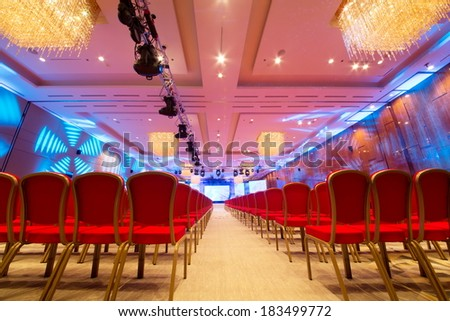 Meeting room with red chairs and colored illumination - stock photo