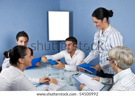 Meeting with five cheerful  business people,a business woman giving all paperwork and they are laughing together,blank chart for presentation in background