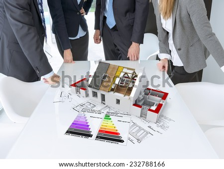 Meeting with people around a table with an architecture model showing roof insulation and energy efficiency charts - stock photo