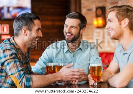 Meeting with the best friends. Three happy young men in casual wear talking and drinking beer while sitting in bar together - stock photo