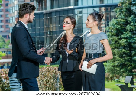 Meeting with the manager. Three successful businessmen in formal dress standing on the street to discuss business and shake hands. Young businessmen talking to each other - stock photo