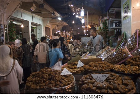 MEKNES - JUL 29: Vendors and customers stand by sweets stall at covered market in Meknes, Morocco on Jul 29, 2010. The market is one of the most important attractions of the city. - stock photo