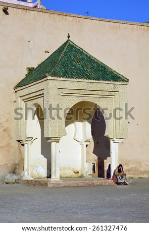 MEKNES, MOROCCO - NOVEMBER 19: Unidentified woman rest in front of the medieval city wall on public place El-Hedim, on November 19, 2014 in Meknes, Morocco - stock photo