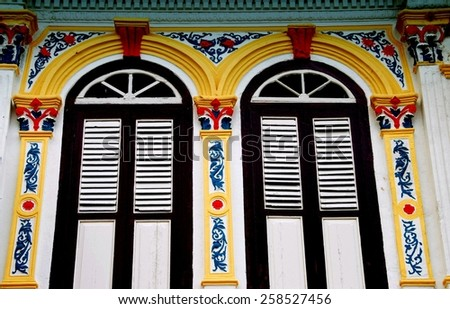 Melaka, Malaysia - December 27, 2006:  Brightly painted pargetted plasterwork pilasters frame louvered shuttered windows on an early 20th century Chinese shop house on Jalan Kaumpung Pantan - stock photo