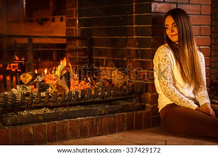 Melancholic pensive woman relaxing resting at fireplace. Thoughtful nostalgic young girl heating warming up. Winter at home. - stock photo