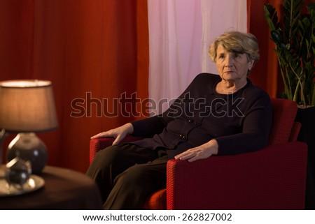 Melancholic senior woman being alone at home - stock photo