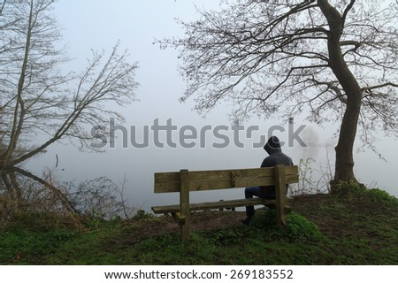 Melancholy emotions concept: depressed man grieving on a bench at a lake on a foggy day. - stock photo