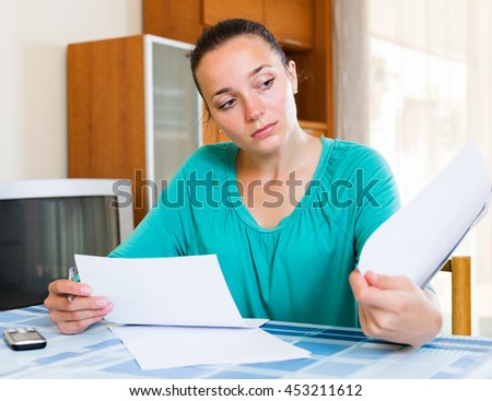 Melancholy woman working with documents at home
