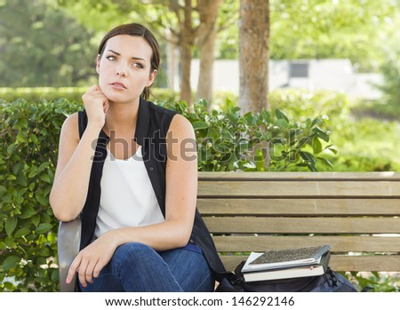 Melancholy Young Adult Woman Sitting on Bench Next to Books and Backpack. - stock photo