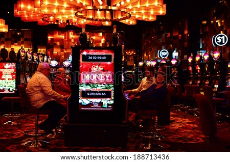 MELBOURNE, AUS - APR 11 2014:Visitors play on Gamble machines at Crown Casino, Melbourne.It's the largest casino complex in the Southern Hemisphere and one of the largest in the world. - stock photo