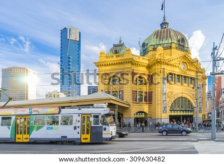 Melbourne, Australia - August 16, 2015: Flinders Street Railway Station in Melbourne with tram, Eureka Tower and other modern buildings near sunset. - stock photo