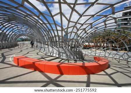 MELBOURNE, AUSTRALIA - FEBRUARY 9, 2009: Person walks along Webb Bridge in Melbourne, Australia. Webb Bridge was designed by D.C. Marshall and received many awards. - stock photo
