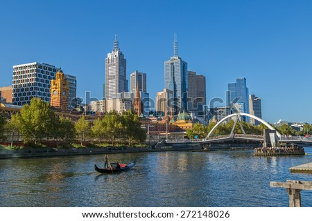MELBOURNE, AUSTRALIA - MARCH 21, 2015: View of the city from Southbank and a romantic ride in a gondola with the gondolier, on Yarra River at autumn season.