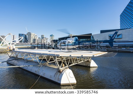 Melbourne, Australia - Nov 13, 2015: Helicopter landed on a floating helipad on Yarra River in Melbourne, ready to take passenger for a scenic tour over downtown Melbourne