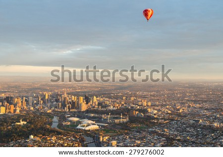 Melbourne, Australia - September 15, 2013: a hot air balloon floating above central Melbourne, the Melbourne Cricket Ground and tennis centre at sunrise. - stock photo