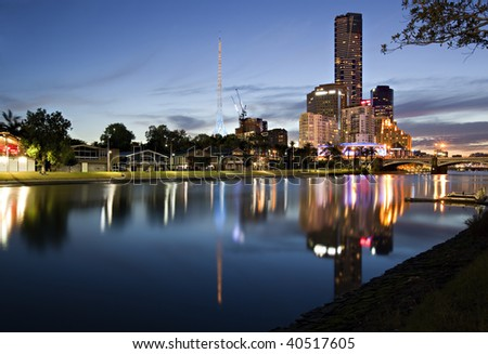 Melbourne, Australia.  Yarra River looking towards Princes Bridge and Southgate.  Rowing boat sheds line the bank. - stock photo