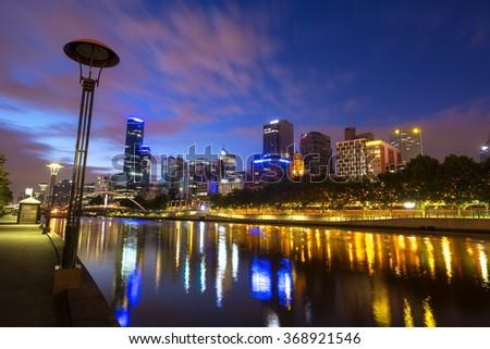 Melbourne CBD cityline at sunset reflecting bright city illumination lights in yarra river. - stock photo