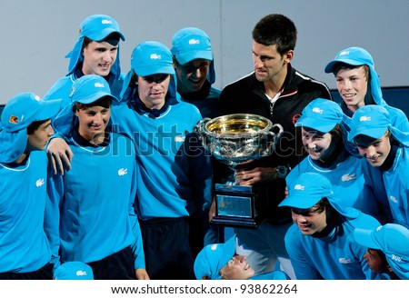 MELBOURNE - JANUARY 29: Novak Djokovic poses with ball kids after his championship win over Rafael Nadal of Spain at the 2012 Australian Open on January 29, 2012 in Melbourne, Australia. - stock photo